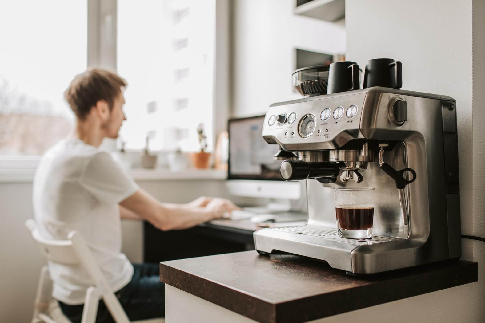 Man working in background with coffee machine on side