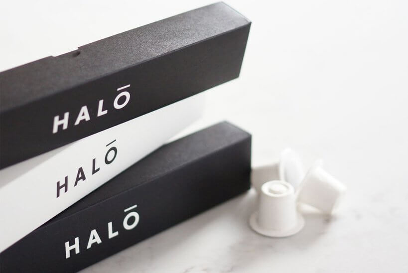 Image shows the Halo coffee pod brand. There are three boxes stacked on top of one another, on the side you can see a couple of the biodegradable coffee capsules.
