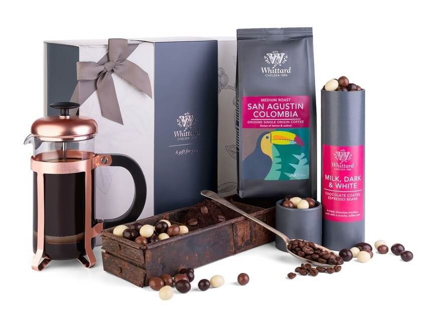Image of gift box filled with coffee gifts. There is a copper French Press and fresh ground coffee presented next to a rustic box, plus you can see some chocolate coated coffee beans spilling out of the gift set.