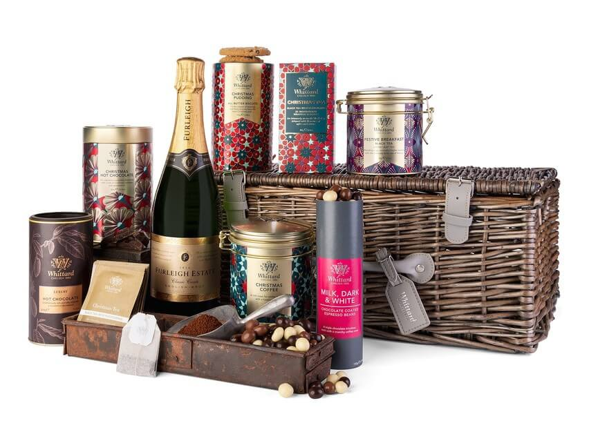 Huge festive gift hamper showing a large wicker basket which presents a number of festive treats, such as Christmas biscuits, teas and coffee. Plus a bottle of fizz! Ground coffee, tea bags and chocolate covered coffee beans are scattered around the photo for presentation purposes.