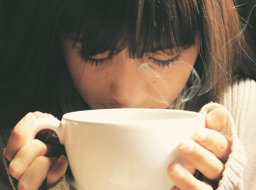 Picture showing woman holding a cup of coffee.